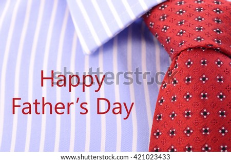 Fathers Day concept with closeup of red mens tie and blue and white stripe shirt business man's attire.  - stock photo
