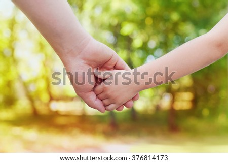 Fathers hand holding his little child in sunny day outdoor, united family and happy childhood concept, beautiful bokeh background - stock photo