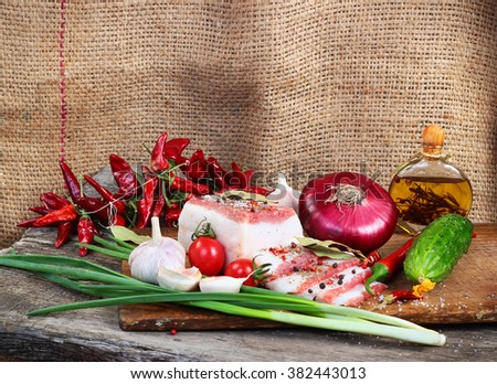 Fatty bacon with green and red vegetables on chopping board against burlap sack background - stock photo