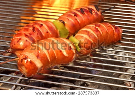 Fatty Sausages On The Hot Barbecue Charcoal Grill And Flames In The Background Closeup - stock photo
