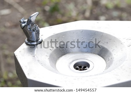 faucet and sink with running water - stock photo