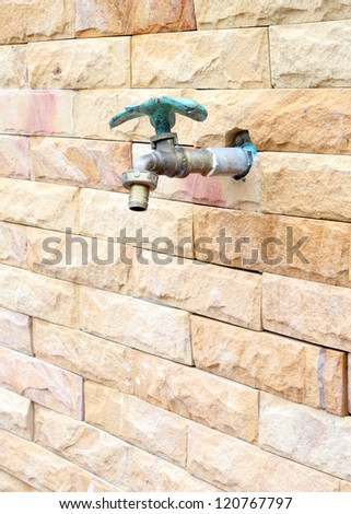 faucet on brick wall background - stock photo