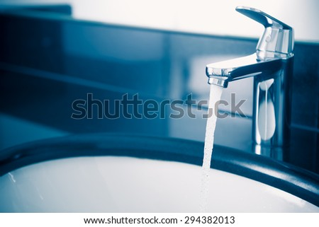 faucet with flowing water, blue tone - stock photo