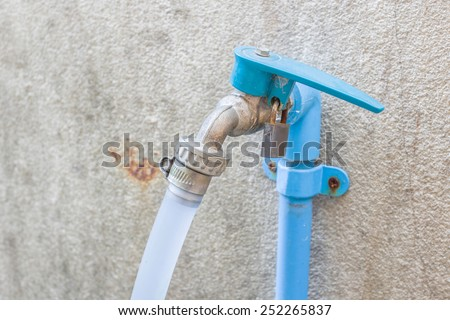 Faucet with rubber tube on wall - stock photo