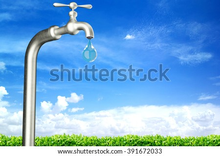 faucet with water drop and blue sky background - stock photo