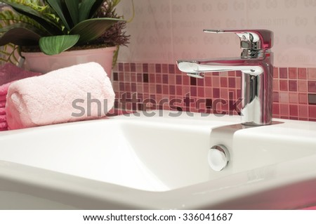faucet with white wash basin with ceramic tile background  - stock photo