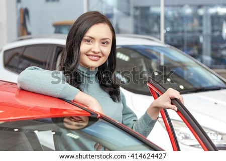 Favorite color. Gorgeous cheerful female client posing near a new car at the car salon smiling happily  - stock photo