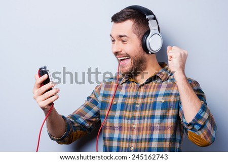 Favorite track. Handsome young man in headphones holding mobile phone and smiling while standing against grey background - stock photo