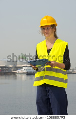 Feamale engineer with hard hat, safety goggles and a safety vest in a harbor district - stock photo