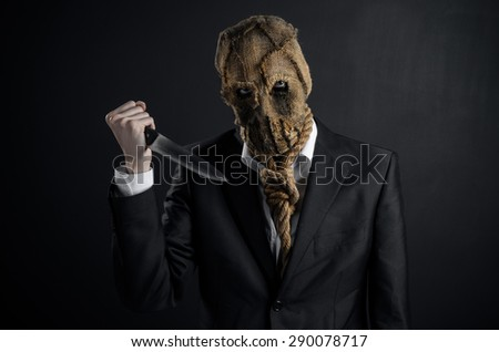 Fear and Halloween theme: a brutal killer in a mask holding a knife on a dark background in the studio - stock photo