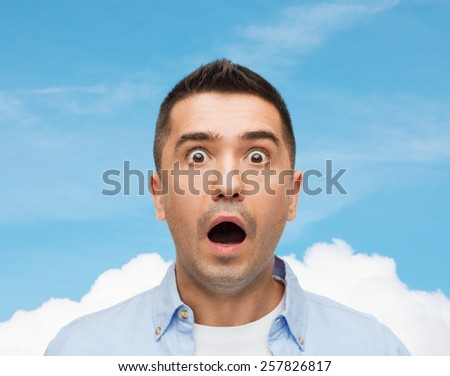 fear, emotions, horror and people concept - scared man shouting over blue sky and cloud background - stock photo