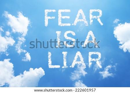fear is a liar cloud word on sky. - stock photo