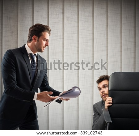 Fearful of boss employee is behind a chair - stock photo
