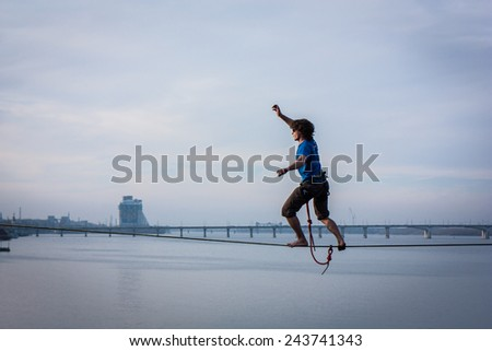 Fearless highliner walking on tight rope over the river in front of the bridge and building with national ukrainian symbol in Dnipropetrovsk, Ukraine - stock photo