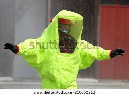 fearless rescuer with the yellow suit against biological hazard from contamination - stock photo
