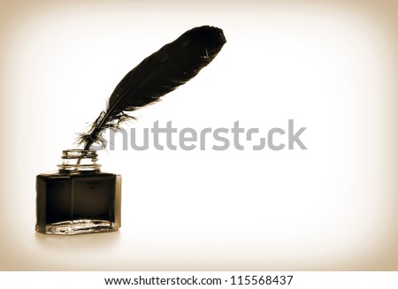 Feather and ink bottle in sepia colors - stock photo