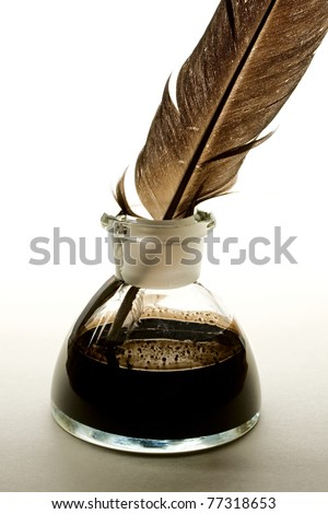 Feather and ink bottle isolated on paper background - stock photo