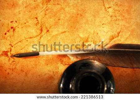 Feather and ink bottle on textured background - stock photo