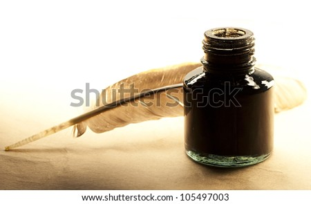 Feather and inkpot on paper - stock photo