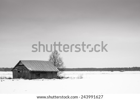 February is a cold month up in the Northern Finland. Even the barn houses seem to look for a warmer place to be. - stock photo