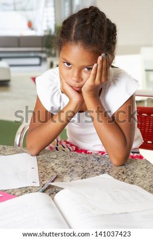 Fed Up Girl Doing Homework In Kitchen - stock photo