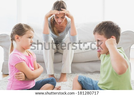 Fed up mother listening to her young children fight at home in the living room - stock photo