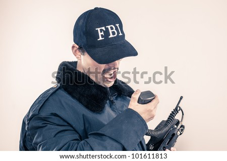 Federal Investigations mustache agent in coat yelling with baseball cap over eyes on vintage radio during crises - stock photo