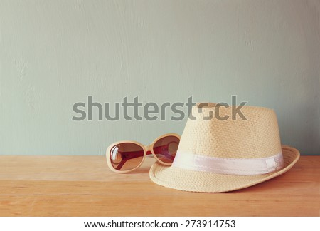 fedora hat and sunglasses over wooden table. relaxation or vacation concept  - stock photo