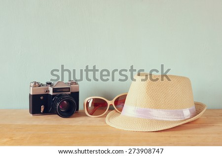 fedora hat, sunglasses old vintage camera over wooden table. relaxation or vacation concept  - stock photo