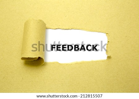 Feedback text appearing behind torn brown paper. - stock photo