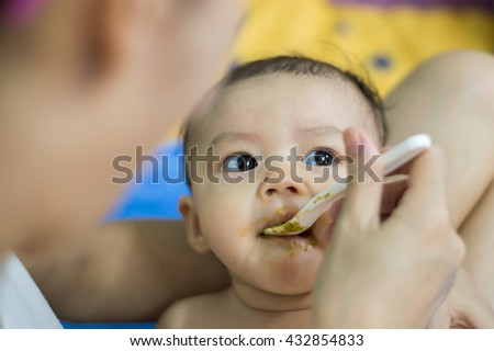 Feeding. Adorable baby child eating with a spoon. Baby's first solid food, Asian baby girl. - stock photo