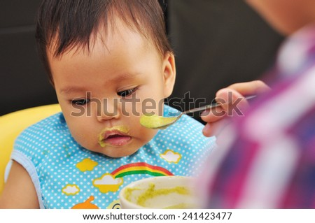 feeding baby food to baby - stock photo