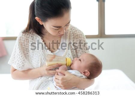 Feeding Baby infant. Asian mother feeding milk to her newborn baby infant with feeding bottle. - stock photo