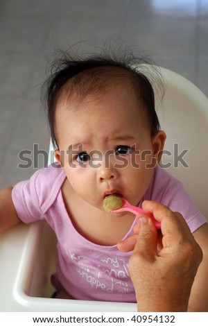 feeding baby with cereal - stock photo