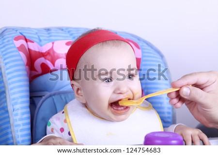 Feeding child can be fun - stock photo