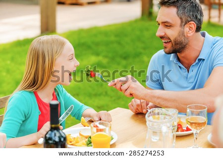 Feeding daughter with fresh salad. Happy young man feeding his daughter with salad while sitting together at the dining table outdoors  - stock photo