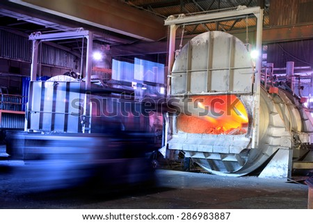 Feeding scrap aluminium in a melting oven in a factory. Recycling. - stock photo