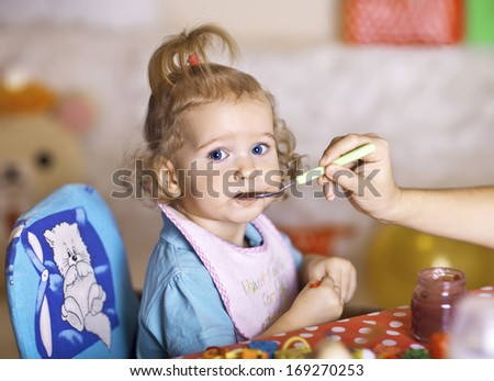 Feeding your baby with a spoon at home - stock photo
