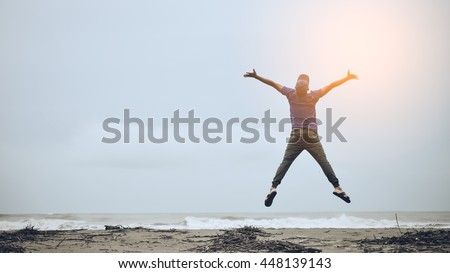 Feel good and freedom concept. Copy space of happy man jumping on beach. Vintage tone color style. - stock photo