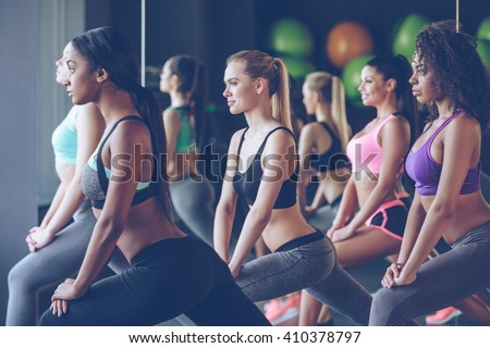 Feel how stretchy you are girls! Side view of beautiful young women with perfect bodies in sportswear exercising with smile at gym  - stock photo