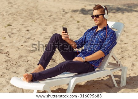 Feel the rhythm. Nice handsome delighted guy lying on the  sun bed and listening to music  while reveling in great time - stock photo