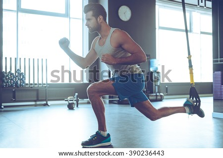 Feel your strength. Full-length side view of young man in sportswear exercising at gym - stock photo