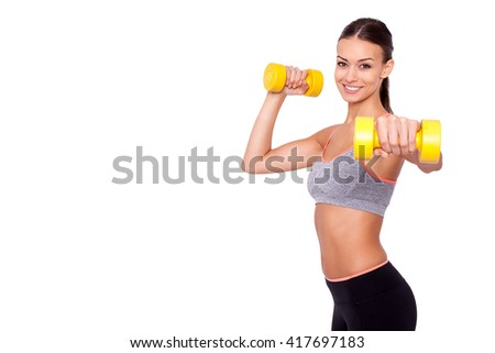 Feeling awesome! Looking even better! Shot of a beautiful and sporty young woman lifting up weights against white background.  - stock photo