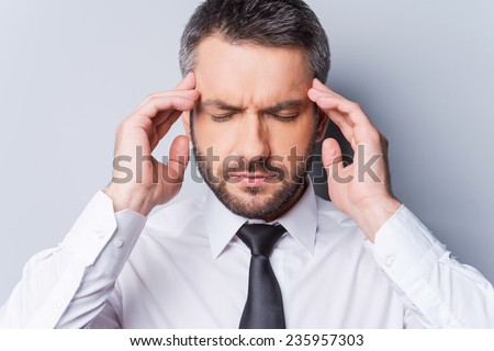 Feeling awful headache. Frustrated mature man in shirt and tie touching his head with fingers and keeping eyes closed while standing against grey background - stock photo