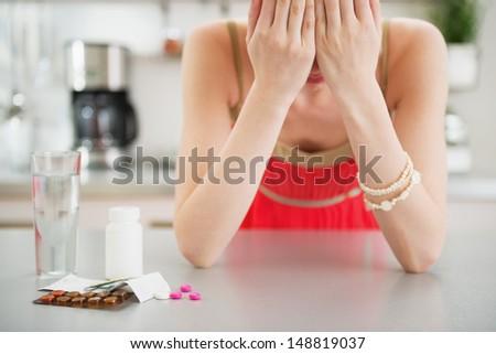 Feeling bad girl and pills on table - stock photo