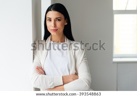 Feeling calm. Beautiful young woman keeping arms crossed and looking at camera while standing near white wall - stock photo