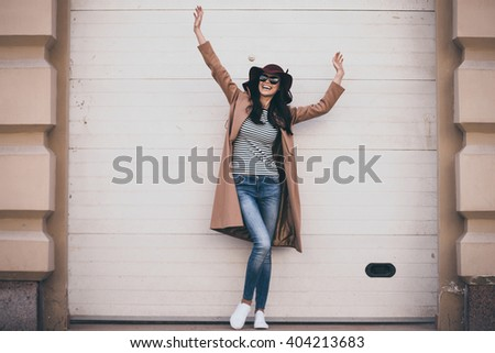 Feeling carefree. Full length of beautiful young woman in sunglasses looking away with smile and keeping arms outstretched while standing outdoors - stock photo
