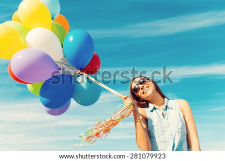 Feeling childlike. Happy young woman holding colorful balloons and smiling while standing against the blue sky - stock photo