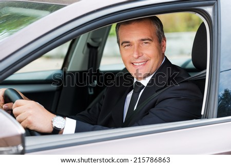 Feeling comfortable in his new car. Cheerful mature man in formalwear driving car and smiling  - stock photo