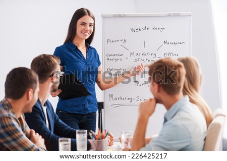 Feeling confident in her speech. Group of business people in smart casual wear sitting together at the table while beautiful woman standing near whiteboard and pointing it with smile - stock photo